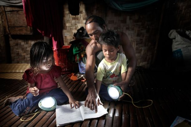 Rural Cambodians make use of a MoonLight, a solar-powered lantern designed to replace the often-dangerous kerosene lamps that are typically found in villages throughout Cambodia and the developing world. The Kamworks lantern uses energy-efficient LED bulbs and is powered by a small solar cell. (Mathieu Young photo)